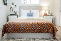 A bedroom in an apartment with a double bed and beside cabinets, and a vivid retro style patterned bed cover.