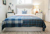 A bedroom in an apartment with a double bed with a colourful checked bed cover