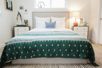 A bedroom in an apartment with a double bed  and a jade green patterned bed cover.