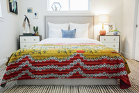 A bedroom in an apartment with a double bed and a retro look antique patterned patchworked bed cover.