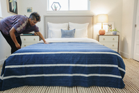 A woman smoothing a blue striped throw over a double bed in a bedroom.   11093010924| 写真素材・ストックフォト・画像・イラスト素材|アマナイメージズ
