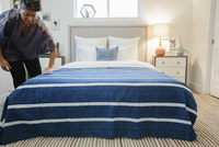 A woman smoothing a blue striped throw over a double bed in a bedroom.   11093010925| 写真素材・ストックフォト・画像・イラスト素材|アマナイメージズ