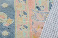 Close up of a fabric bedspread or throw, with different fabrics sewn and quilted, a retro style and faded look.