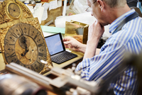 A clock maker in his workshop using a laptop.