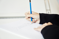 A woman working on a graphic on a drawing board, outlining letters with a pencil.