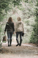 Two women walking in coats and boots along a country path with a basket.
