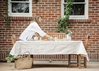 A woman standing by a table, preparing eggs for breakfast.  11093011241| 写真素材・ストックフォト・画像・イラスト素材|アマナイメージズ