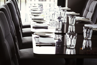Close up of dining tables set with glasses, plates, cutlery and napkins in a restaurant.
