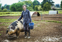 A woman stood by a large pig holding a bucket. 11093011588| 写真素材・ストックフォト・画像・イラスト素材|アマナイメージズ