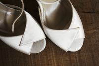 A pair of white peep toed shoes. Close up of wedding shoes.
