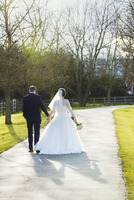 A bride and groom on their wedding day walking arm in arm down a path in the sunshine, rear view.