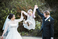A bride and bridegroom, a couple on their wedding day holding and swinging a little girl in the air between them.