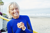 Smiling senior woman wearing a wetsuit, standing on a sandy beach.