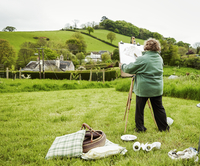 A woman artist standing outdoors at an easel, painting a rural scene.