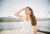 Woman with long brown hair standing on a sail boat.