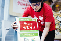 The ramen noodle shop. A man putting out the advertising board and menu on the sidewalk.