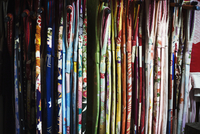 Rows of colourful fabric hanging up, traditional kimonos, a robe with wide sleeves, traditional style.