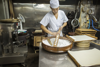 A small artisan producer of wagashi. A man mixing a large bowl of ingredients and pressing the mixed dough into moulds in a comm