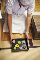 A small artisan producer of specialist treats, sweets called wagashi. A chef presenting a tray of selected wagashi of different