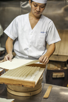 A small artisan producer of specialist treats, sweets called wagashi. a chef covering a tray of small moulded sweets for drying.