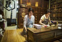 A traditional wagashi sweet shop. A woman working at a desk using a laptop and phone. A woman packing merchandise.