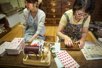 A small artisan producer of specialist treats, sweets called wagashi. Two women working packing sweet boxes for delivery.