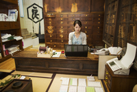 A traditional wagashi sweet shop. A woman working at a desk using a laptop and phone.   11093012367| 写真素材・ストックフォト・画像・イラスト素材|アマナイメージズ