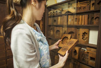 A small artisan producer of specialist treats, sweets called wagashi. A woman holding shaped wooden moulds used in the productio