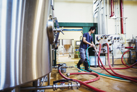 Man working in a brewery, connecting hoses to a metal beer tank.
