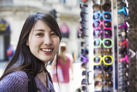 A Japanese woman trying on sunglasses in London, a summer tourist visitor.