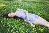 Young woman with long brown hair lying on a lawn.