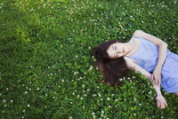 Young woman with long brown hair lying on a lawn. 11093012652| 写真素材・ストックフォト・画像・イラスト素材|アマナイメージズ