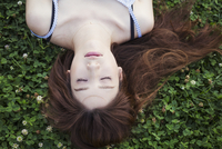 Young woman with long brown hair lying on a lawn. 11093012653| 写真素材・ストックフォト・画像・イラスト素材|アマナイメージズ