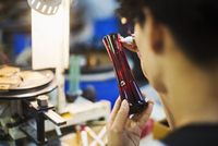A craftsman in a glass maker's workshop inspecting a red glass vase and marking the exterior. 11093012694| 写真素材・ストックフォト・画像・イラスト素材|アマナイメージズ