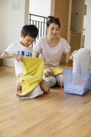 Family home. a woman and her son sorting and folding clean laundry.