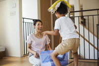 Family home. A woman and her son sorting the laundry, the boy balancing towels on his head.  11093012783| 写真素材・ストックフォト・画像・イラスト素材|アマナイメージズ