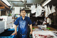 A traditional fresh fish market in Tokyo. A man in a blue apron standing behind the counter of his stall.  11093012840| 写真素材・ストックフォト・画像・イラスト素材|アマナイメージズ