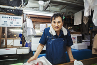A traditional fresh fish market in Tokyo. A man in a blue apron standing behind the counter of his stall.  11093012843| 写真素材・ストックフォト・画像・イラスト素材|アマナイメージズ