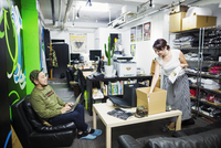 Design Studio. Two colleagues, man and woman, stocktaking and packing goods for sale and distribution. Teeshirts and hats.  11093012856| 写真素材・ストックフォト・画像・イラスト素材|アマナイメージズ