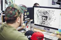 Design Studio. A man seated at a desk using a computer to design tee shirt prints. 11093012859| 写真素材・ストックフォト・画像・イラスト素材|アマナイメージズ