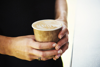 Close up of woman holding coffee in a paper cup.
