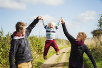 Parents holding a small boy's hands and lifting him up in the air.