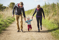 Parents and a child walking along a footpath in the countryside. 11093013155| 写真素材・ストックフォト・画像・イラスト素材|アマナイメージズ