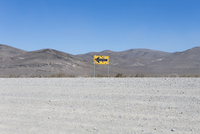 Bullet riddled arrow sign in desert, Black Rock Desert, Nevada