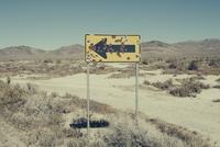 Bullet riddled arrow sign in desert, Black Rock Desert, Nevada