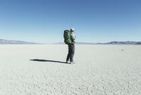 Male backpacker hiking in vast desert, Black Rock Desert, Nevada 11093013392| 写真素材・ストックフォト・画像・イラスト素材|アマナイメージズ