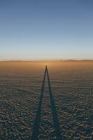 Man standing on Black Rock Desert Playa at dusk, casting long shadow, Nevada
