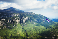 A paraglider in flight over a valley in the mountains.