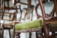 A stack of antique chairs, with fraying seas for refurbishment.