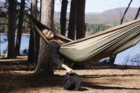 A woman lying in a hammock relaxing, under the pine trees by a lake. 11093013595| 写真素材・ストックフォト・画像・イラスト素材|アマナイメージズ
